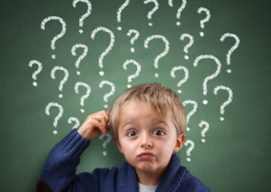 Child scratching head with question mark on blackboard concept for confusion, brainstorming and choice