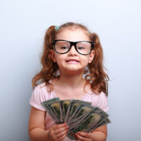 Fun emotional small kid girl in glasses holding and showing dollars. Happy winner on blue background with empty copy space