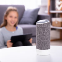 Close-up Of A Wireless Speaker On Furniture With Girl In Background