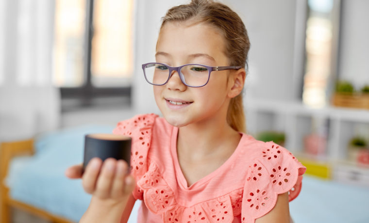 children, education and technology concept - student girl using smart speaker at home