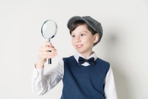虫眼鏡を見る少年