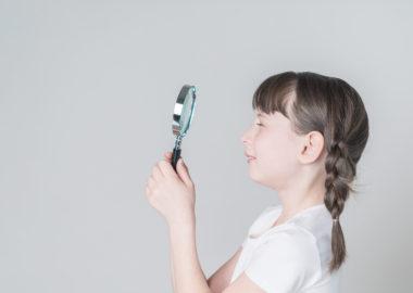 虫眼鏡を見る少女