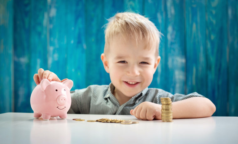 three years old child sitting st the table with money and a piggybank. Happy boy with euro coins