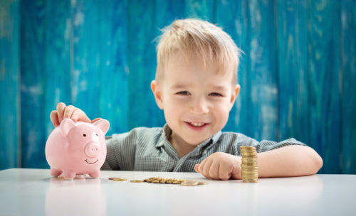 three years old child sitting st the table with money and a piggybank